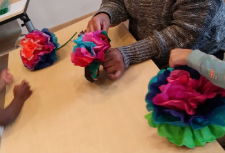 multicolor tissue paper flowers being made by one pair of brown adult hands, and two pairs of brown kids hands.