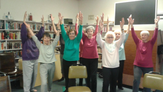 numerous seniors stretching in a library