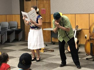 photo of woman reading book while man plays harmonica