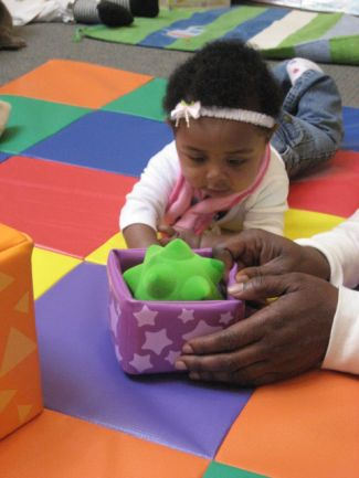 baby on tummy looking at box with adult hands holding the box