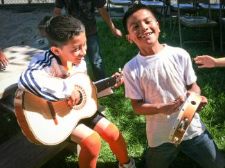 photo of young boy playing guitar and another boy smiling playing tamborine