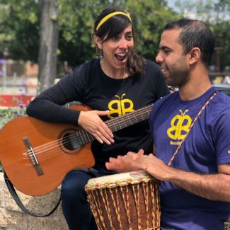 photo of Baila Baila band members Isa playing a guitar and Rico playing a drum