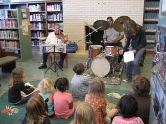 photo of performers at JazzArt with children listening
