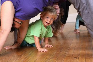 Child crawling under grown-up in a downward-facing dog pose. CC Jessica Lucia https://www.flickr.com/photos/theloushe/3988309695