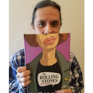 Person holding a book with the face of Mick Jagger as the cover.