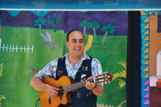 photo of Juan L. Sanchez playing guitar in front of a colorful background