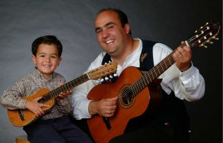 Photo of little boy and Juan L. Sanchez both holding guitars and smiling