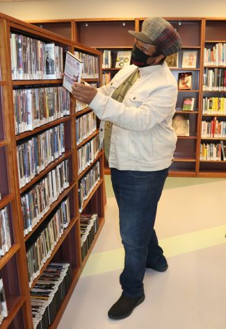 man in front of book shelf looking at books wearing a mask