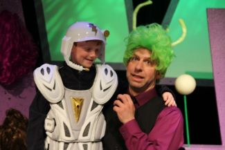 photo of Kenn Adams with an alien wig on kneeling next to a smiling child with a space trooper uniform on.