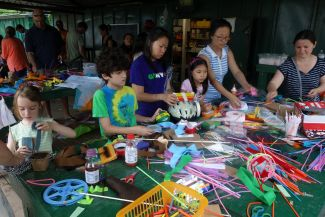 photo of kids and adults crafting bicycle helmets; photo by Nick Normal licensed under CC BY-NC-ND 2.0