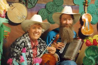 photo of Jeanie McLerie holding a fiddle and Ken Keppeler holding an accordion both wearing cowboy hats