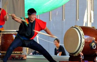 photo of Taiko drummer Kristy Oshiro playing the taiko drums; photo credit Dogmatix Kate