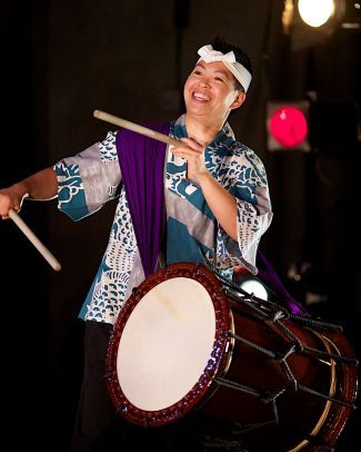 picture of Kristy Oshiro playing taiko drum that is attached by a sling; permission of Kristy Oshiro