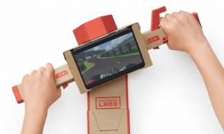 Cardboard handlebars with a Nintendo switch showing a race track mounted in the center and hands on both handles
