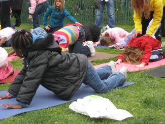 photo of children doing yoga outside wearing coats