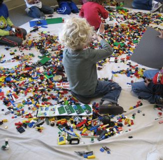 photo of a patron sitting amongst LEGOs