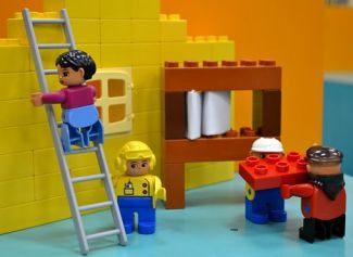 Construction site with 4 construction workers made of Lego blocks