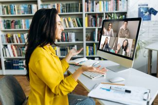 Woman in yellow talking on Zoom call with 4 other people on the computer screen.