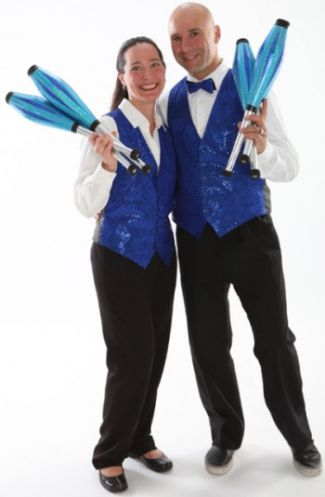 Earthcapades duo wearing blue vests and holding juggling pins