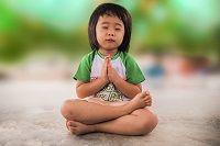 photo of child sitting in lotus yoga pose