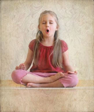 photo of child sitting in lotus pose while chanting