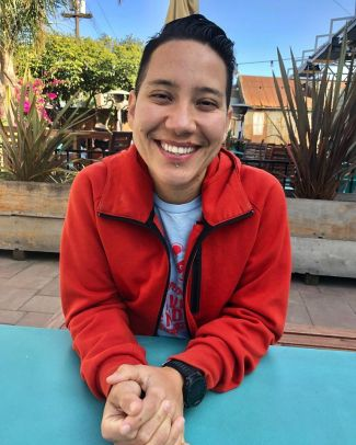 photo of author Lourdes Rivas sitting outside at a blue table wearing a red coat and smiling