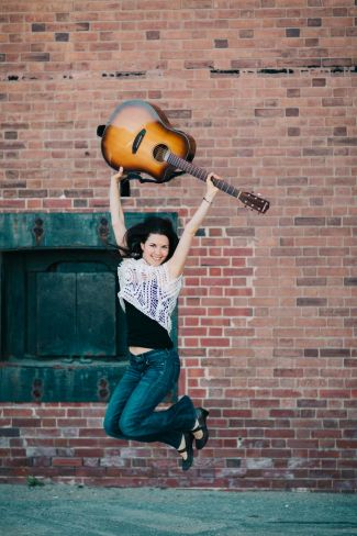 photo of musician Megan Schoenbohm jumping in the air holding her guitar up