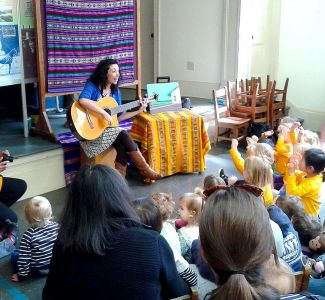photo of children's musician Mariela Herrera performing to audience of kids