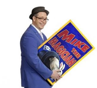 photo of Mike the Magician carrying billboard that says Mike the Magician