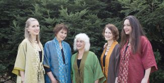 The Mozaik Ensemble standing in front of evergreen trees