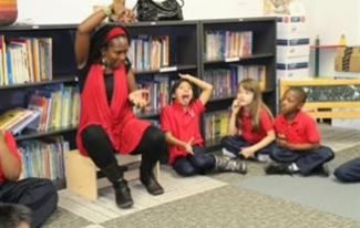 photo of Muriel Johnson telling a story while kids look on and hold their arms like hers