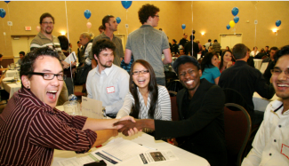 several smiling people shaking hands across a table