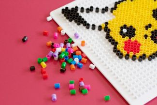 Perler beads being arranged on a board to make a picture of Pikachu