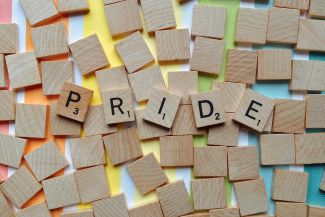 """Pride"" in scrabble tiles over a rainbow."