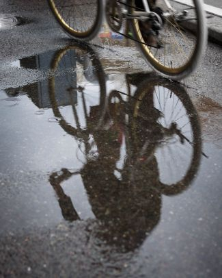 Bike and rider reflected in a puddle of water.