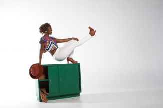 photo of dancer Quynn Johnson on top of green locker balancing on one bent leg, kicking out the other leg in front of her
