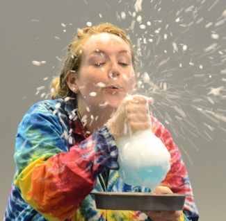 photo of presenter blowing foam off the top of a beaker