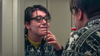 Taylor 'T.B.' Harmon shaving their face in the mirror.