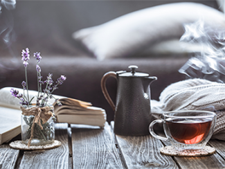 Cup of tea, lavender in a jar, open book and a sweater on a coffee table