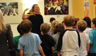 photo of opera singer/educator talking to kids in audience at SF Opera Guild Sing a Story program