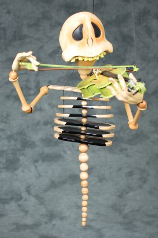 photo of a skeleton marionette playing a violin