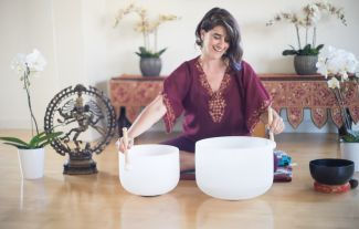 Melissa Felsenstein smiling while using two large singing bowls.