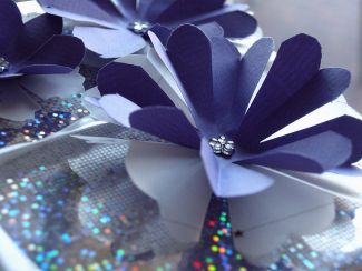 dark blue flower made of stacked layers with a shiny bead in the center - photo by Flickr user PermaCultured