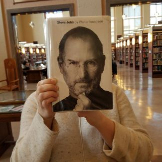 Person holding a book with the face of Steve Jobs as the cover