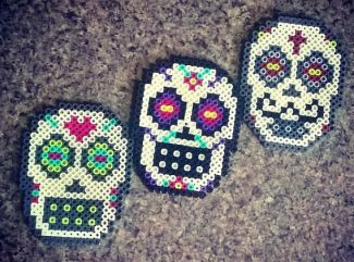 A picture of three sugar skulls made out of perler fuse beads