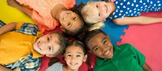 five smiling children lying on their backs on a colorful mat