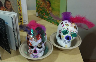 Two papier mache skulls painted white and decorated with brightly colored feathers, sequins and more.