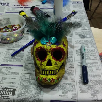 Papier mache skull painted yellow and decorated with brightly colored feathers, sequins and more.