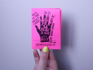 Hand with lime green fingernail polish holding a zine with hot pink cover with hand drawing.
