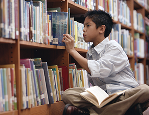 Boy looking at a shelf of books
